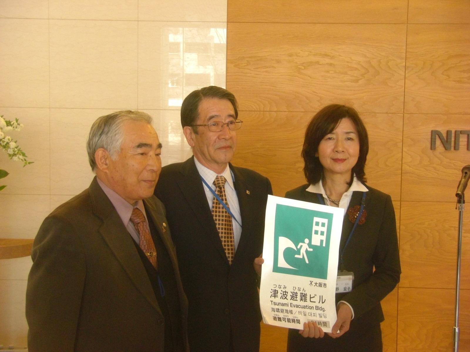 ステッカーを贈る浅野区長。中央はニッタの國枝社長