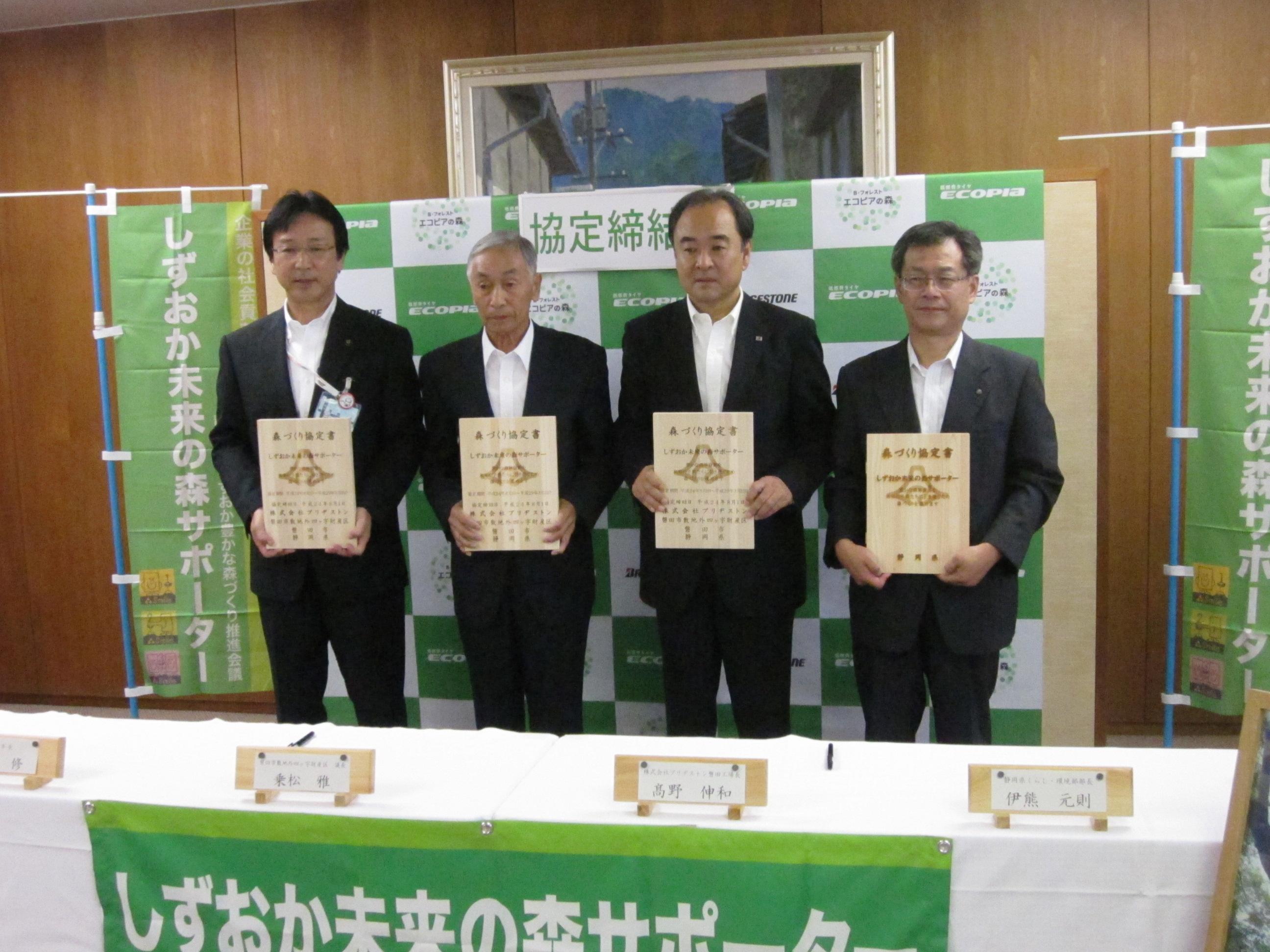 サインした協定書を持つ左から渡部磐田市長、乗松磐田議会長、高野伸和ブリヂストン磐田工場長、伊熊静岡県環境部長