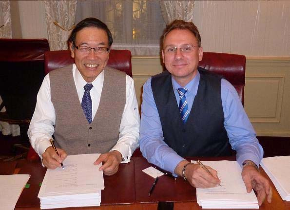 調印式で記念写真に納まる西村社長(左)とOlaf Hahn CEO