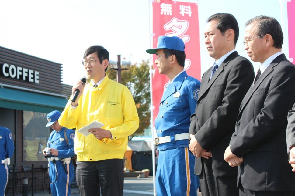 あいさつする奥田専務理事(左)