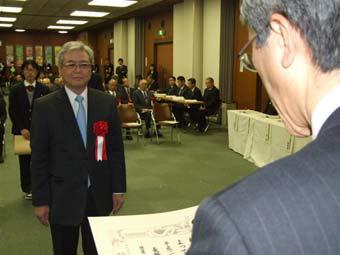 表彰式に臨む尾崎副社長(左)