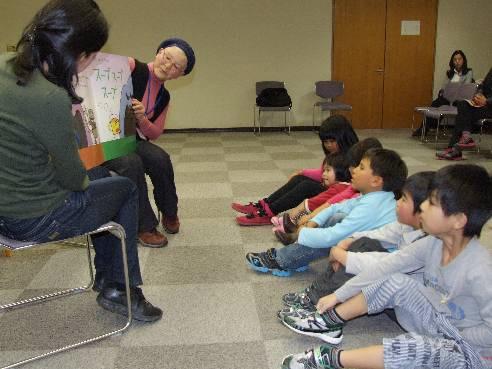 指導員が読み聞かせる絵本に興味津々の児童