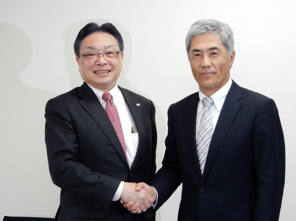 握手する津谷前会長(左)と野地新会長(右)
