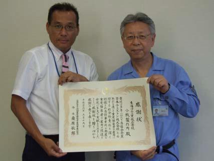 感謝状を手にする臼井社長(左)と田中睦・小牧製作所長