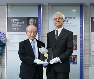 赤﨑教授(左)からレプリカを寄贈される荒島社長