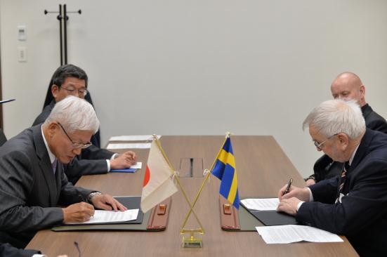 調印式で契約書に署名するホルムストーム氏(右)と社長兼COO松井氏