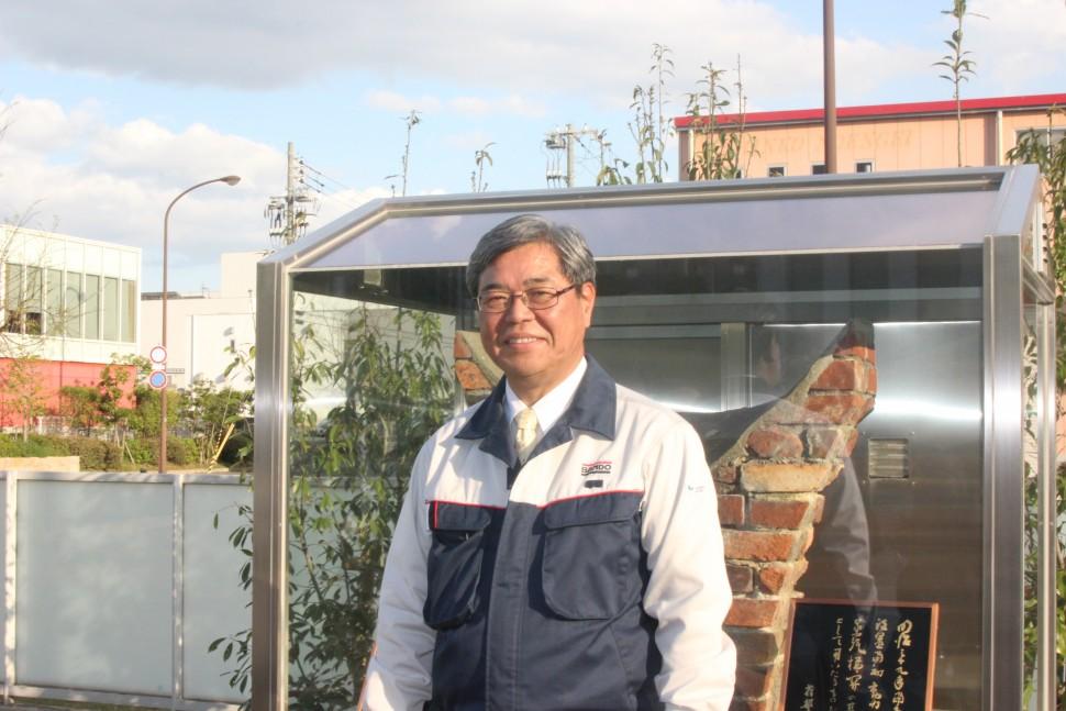 モニュメントの前で記念撮影に応じる吉井社長
