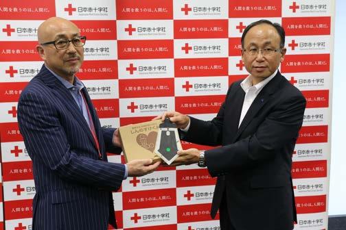 大橋専務(右)から心臓マッサージの訓練をサポートするシステム「しんのすけくん」を受け取る見澤事業局長