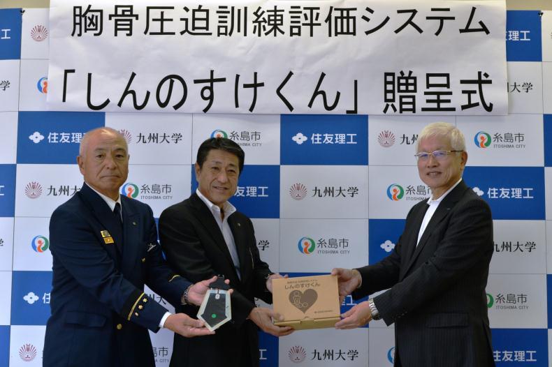 松井社長(右)からしんのすけくんを受け取る月形市長(中央)と濵地消防長