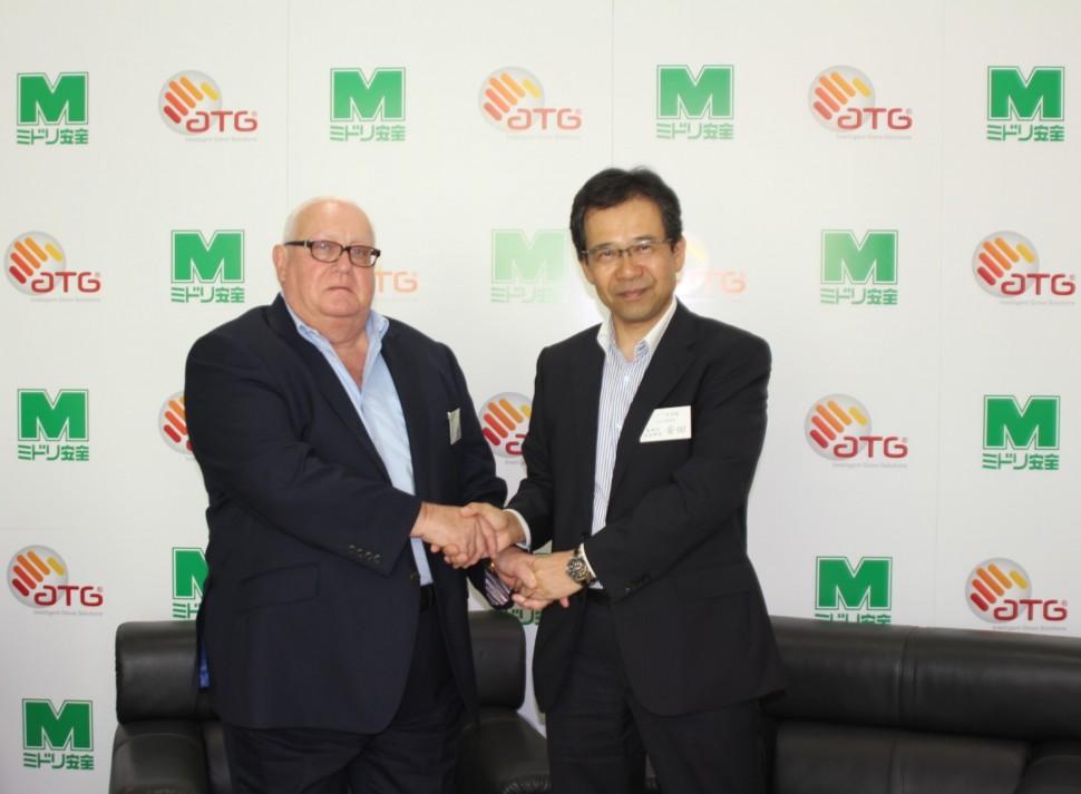 調印を記念して握手する安田氏とジョーンテイラーATG社チェアマン、CEO