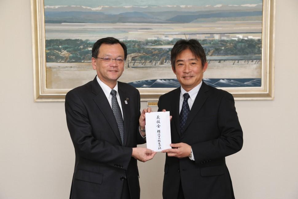 落合克宏平塚市長(左)に義援金を手渡す小林一司執行役員平塚製造所長