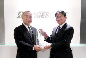 クラリベイト アナリティクの日野・日本代表(左)からトロフィーを贈られる 荒木充・知的財産本部長