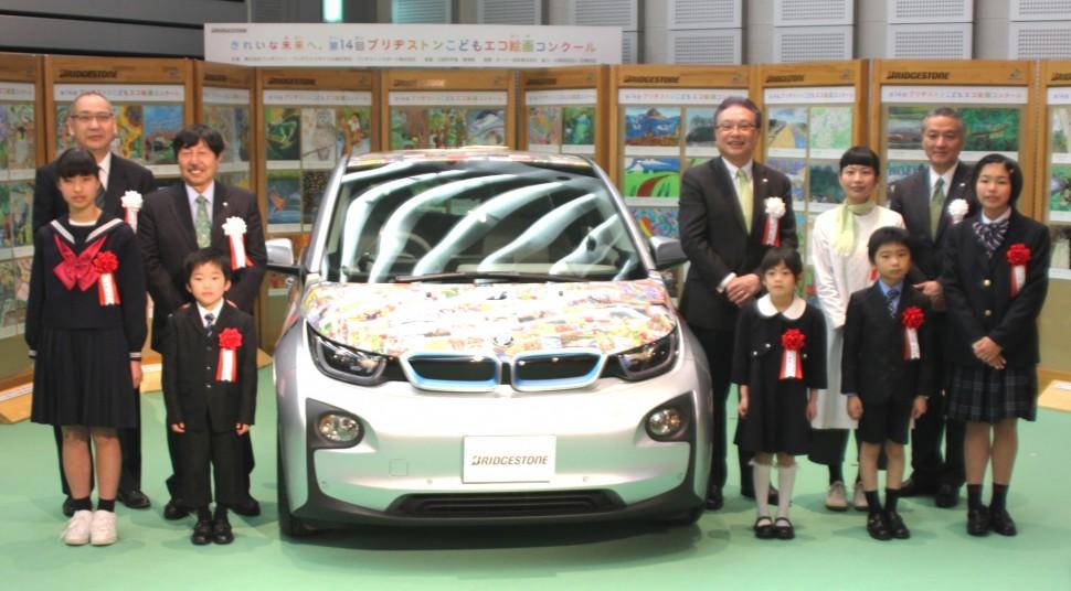 受賞作をラッピングした車とともに記念撮影に収まる受賞者と審査員