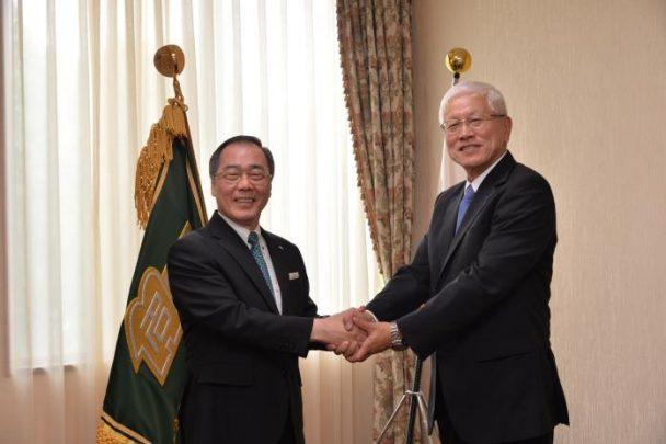 固い握手を交わす松尾総長(左)と松井社長