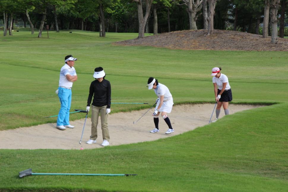 ゴルフ場体験会でバンカーの指導を受ける参加者