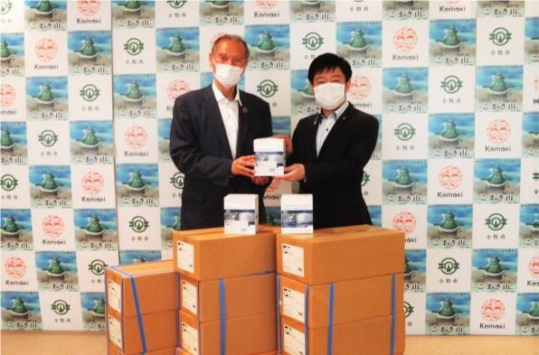 寄贈式で清水社長(左)からマスクを受け取る山下市長