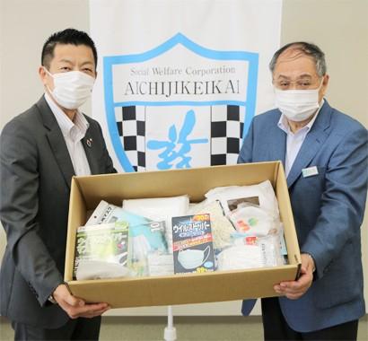 愛知慈恵会の谷川理事長(右)にマスクを手渡すTGロジスティクスの斉藤社長