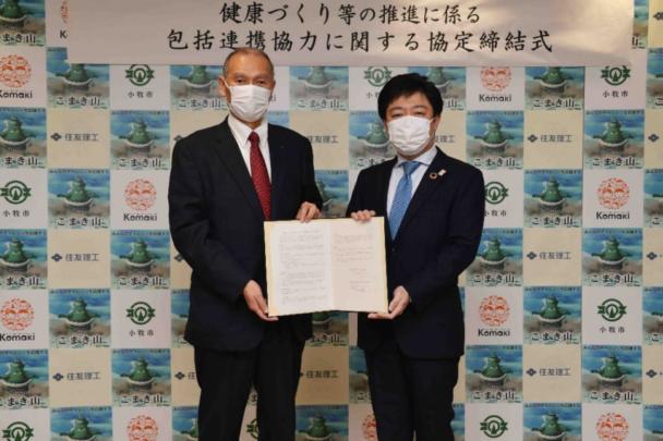 協定締結式で記念撮影に応じる山下市長(右)と清水社長