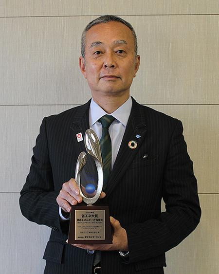 受賞トロフィーを持つ村岡常務執行役員