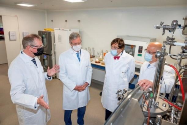 実験室見学の様子(左からヤンセン社長、フィリップ陛下、ディルポ首相、研究員)