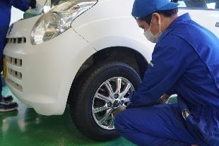 寄贈車両にタイヤを装着する学生